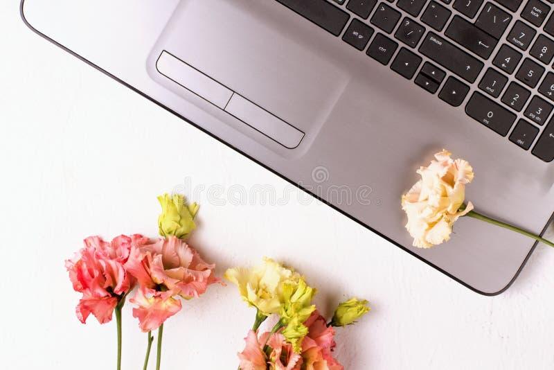 Tabla blanca con el ordenador port?til y las flores Espacio de trabajo del Freelancer fotografía de archivo libre de regalías