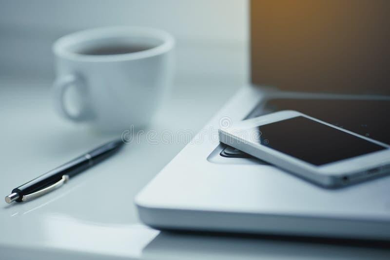 Tabla blanca de la oficina con el ordenador portátil, el café, el smartphone y la pluma foto de archivo