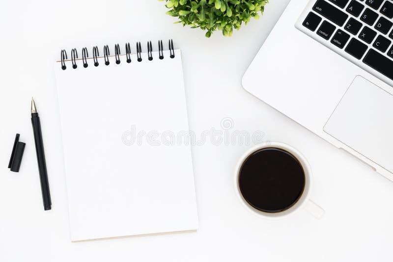 Tabla blanca del escritorio de oficina con la página en blanco del cuaderno con la pluma, el ordenador portátil y el café Visi?n  fotografía de archivo libre de regalías
