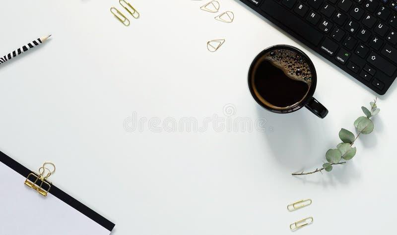 Tabla blanca del escritorio de oficina con la taza del ordenador portátil de café y de fuentes foto de archivo libre de regalías