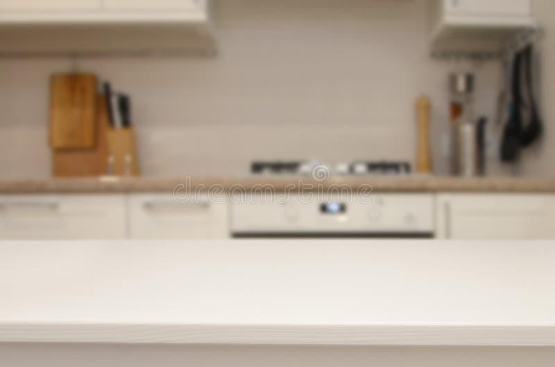 Tabla blanca en el fondo del interior borroso de la cocina fotos de archivo libres de regalías