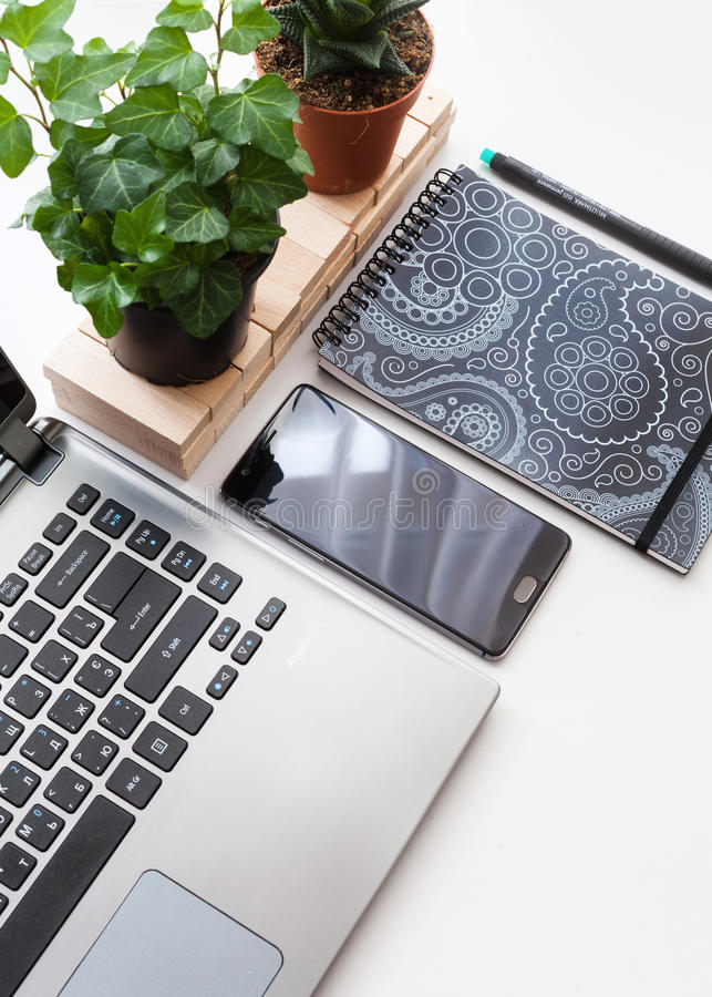 Tabla blanca moderna del escritorio de oficina con el ordenador portátil, smartphone con la pantalla negra y plantas Visión super fotos de archivo libres de regalías