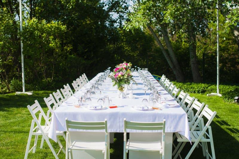 Tabla blanca y larga de la boda del arte al aire libre foto de archivo