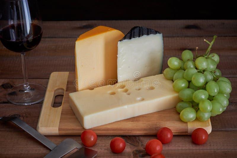Tabla con diversos quesos y copa de vino en fondo oscuro imagen de archivo
