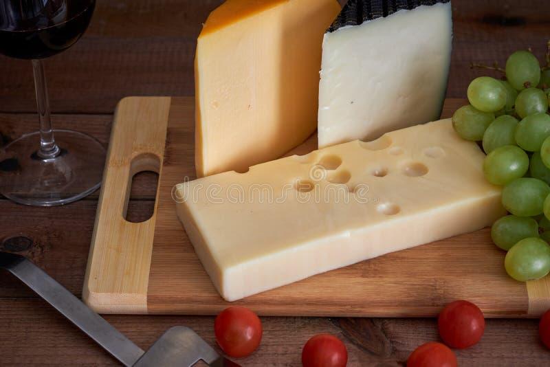 Tabla con diversos quesos y copa de vino en fondo oscuro fotos de archivo
