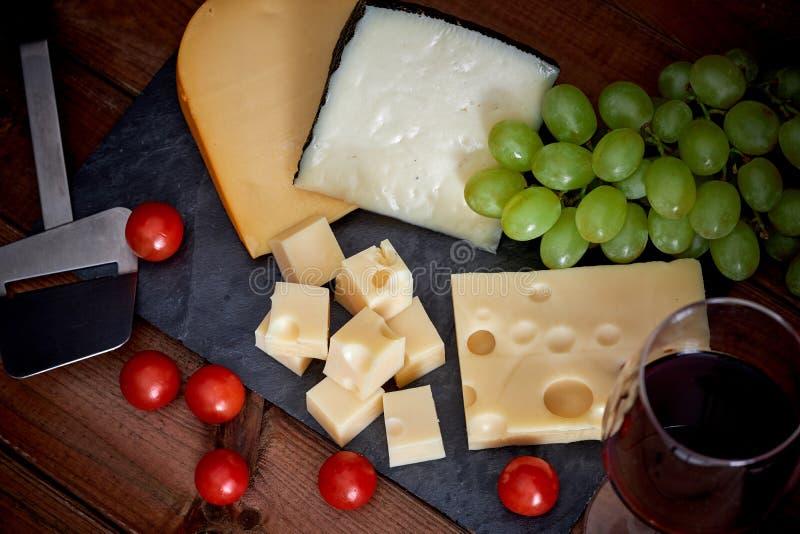 Tabla con diversos quesos y copa de vino en fondo oscuro imagenes de archivo