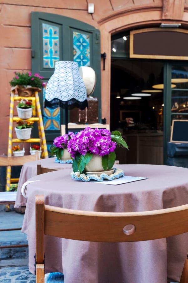 Tabla con el mantel y florero con las flores rosadas en el café de la terraza del verano foto de archivo libre de regalías