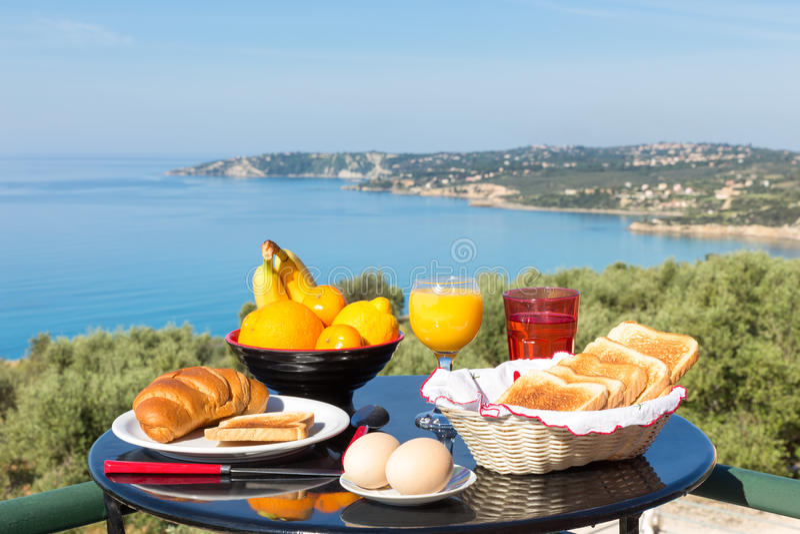 Tabla con la comida y bebidas delante del mar y de la playa azules foto de archivo libre de regalías