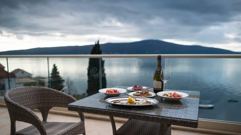 Tabla con la comida y el vino locales en el balcón casero fotografía de archivo