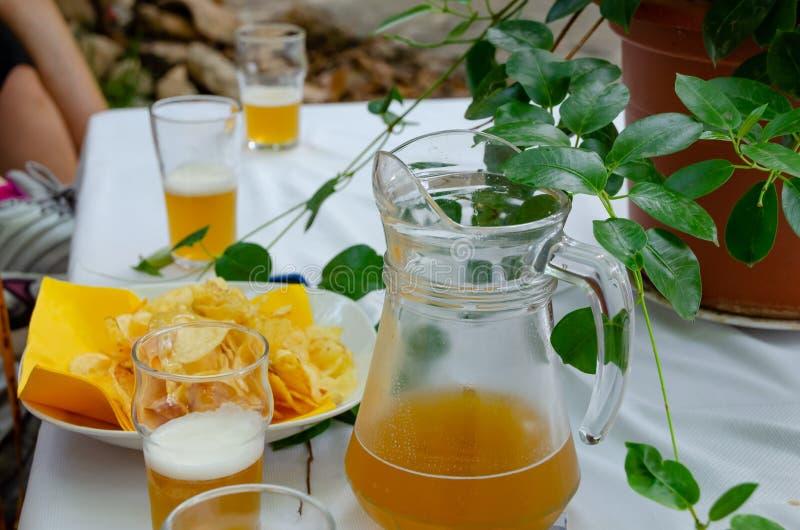 Tabla con la taza, los vidrios y las patatas de cerveza del arte foto de archivo
