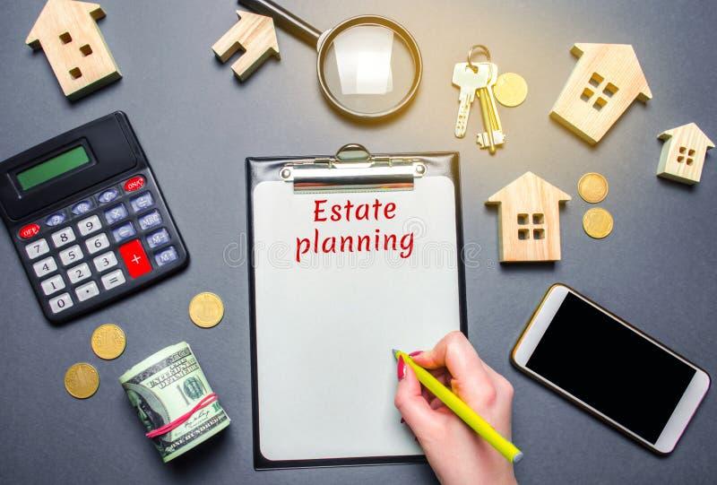 Tabla con las casas de madera, calculadora, lupa con el planeamiento de estado de la palabra Propiedad insurance hipoteca inversi imagen de archivo