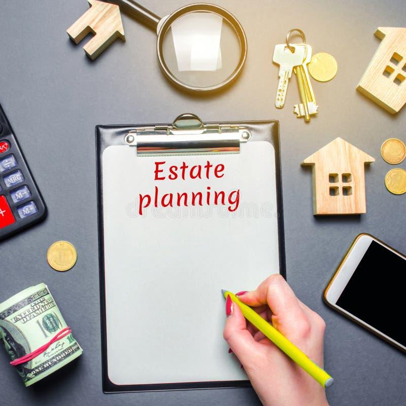 Tabla con las casas de madera, calculadora, lupa con el planeamiento de estado de la palabra Propiedad insurance hipoteca inversi foto de archivo