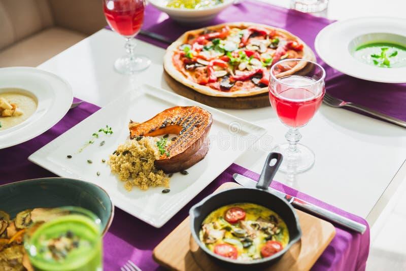 Tabla con los platos vegetarianos - pizza, ensaladas, sopa, empanada y bebidas Comida en restaurante fotografía de archivo
