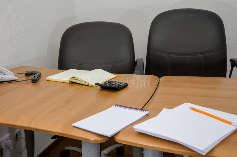 Tabla con una silla, calculadora, cuaderno, efectos de escritorio de la oficina fotografía de archivo libre de regalías
