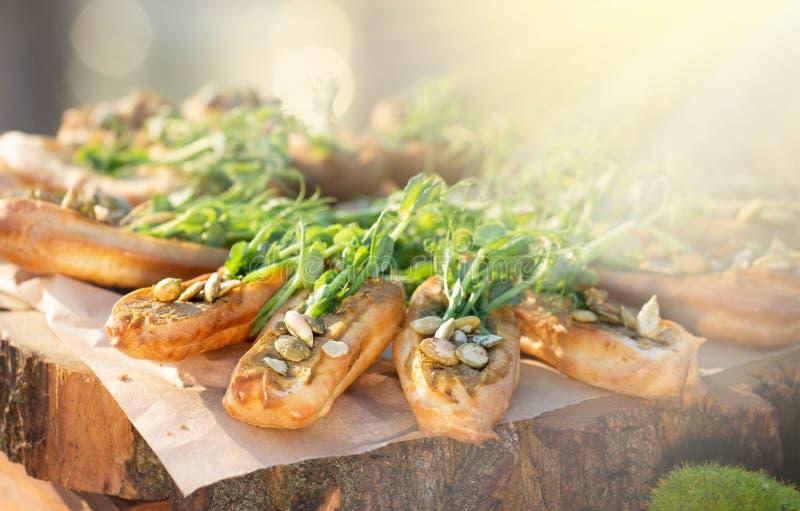 Tabla de banquete de abastecimiento maravillosamente adornada con bocados y aperitivos sanos de la comida con el bocadillo, en la imagen de archivo