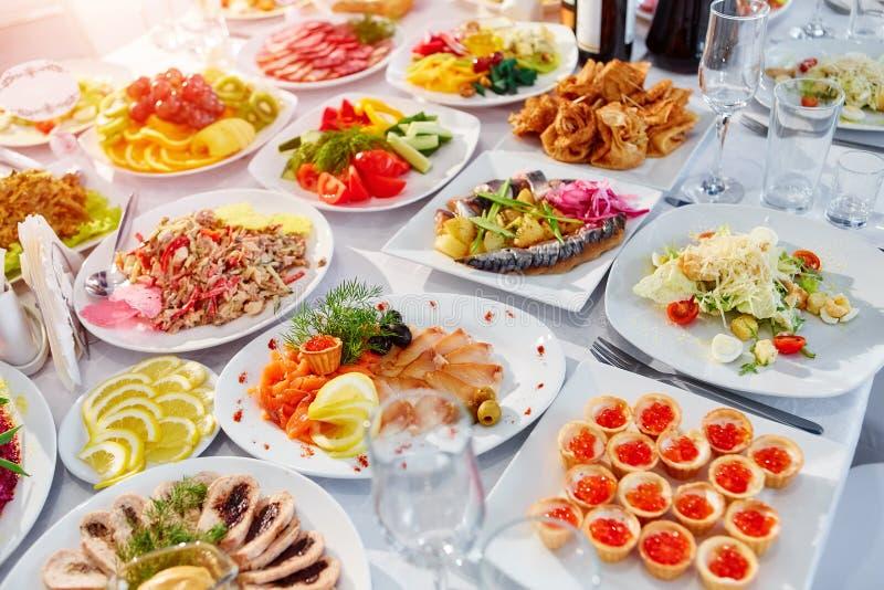 Tabla de banquete de abastecimiento maravillosamente adornada con diversa comida foto de archivo