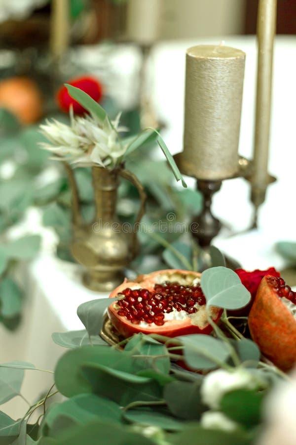 Tabla de banquete festivamente adornada en el restaurante Las flores frescas son velas de oro y sillas y granate rojos costoso ri foto de archivo libre de regalías