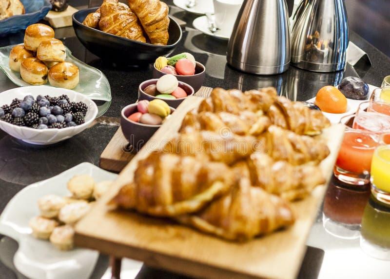 Tabla de buffet del desayuno con los scones de los macarrones del jugo y bayas y cruasanes fotos de archivo libres de regalías