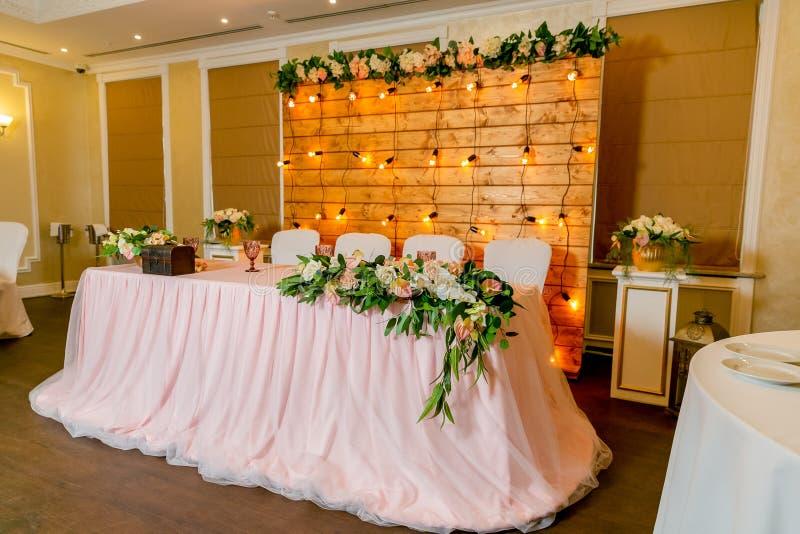 Tabla de cena blanca hermosa para los recienes casados adornados con verdor y el pa?o largo E imagen de archivo libre de regalías