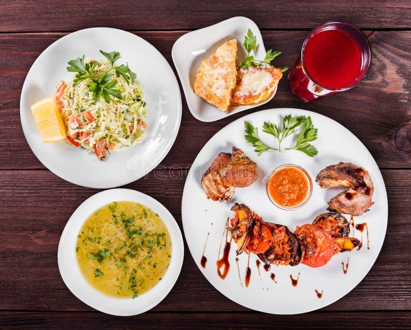 Tabla de cena deliciosa con la carne y las verduras asadas a la parrilla, la ensalada de las verduras frescas, la sopa de pollo,  foto de archivo