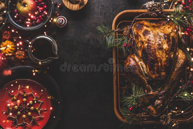 Tabla de cena de la Navidad con el pavo asado entero, relleno con las frutas secadas servidas con la salsa, placas rojas, cubiert fotos de archivo