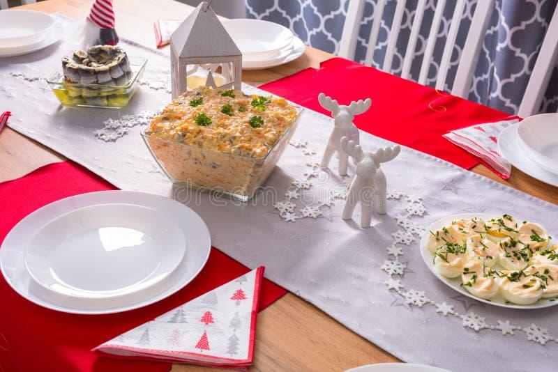 Tabla de cena de la Navidad con las verduras ensalada y la mayonesa de los huevos imagen de archivo libre de regalías