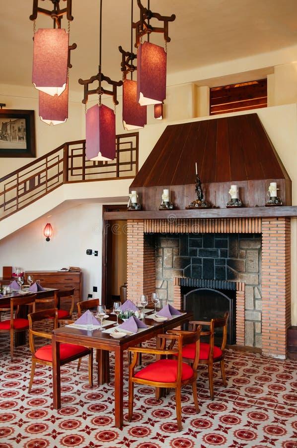 Tabla de cena de las sillas de la chimenea vieja retra del ladrillo del vintage y lámpara de madera del techo imagen de archivo