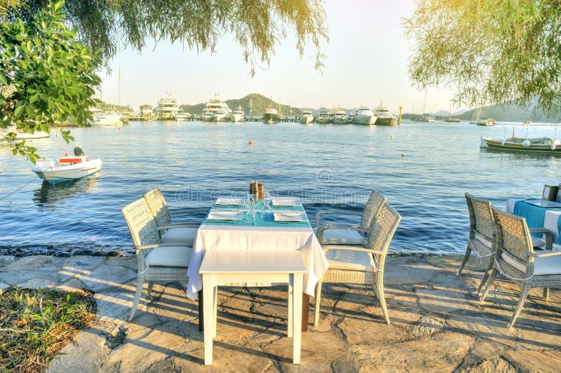 Tabla de cena romántica por la playa, tabla al aire libre de un restaurante de la playa en Gocek Turquía fotos de archivo