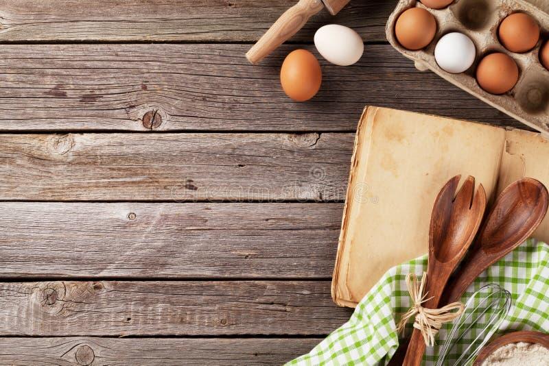 Tabla de cocina con el libro de cocina, los utensilios y los ingredientes foto de archivo