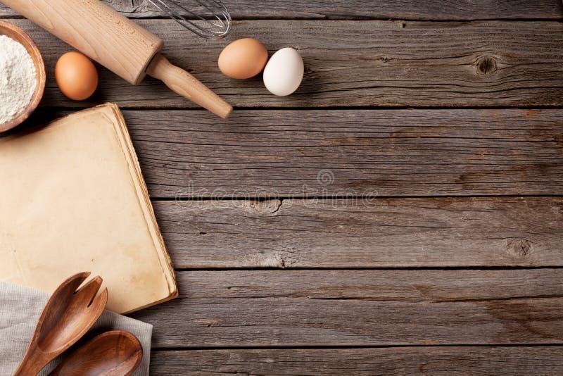 Tabla de cocina con el libro y los utensilios de la receta imágenes de archivo libres de regalías
