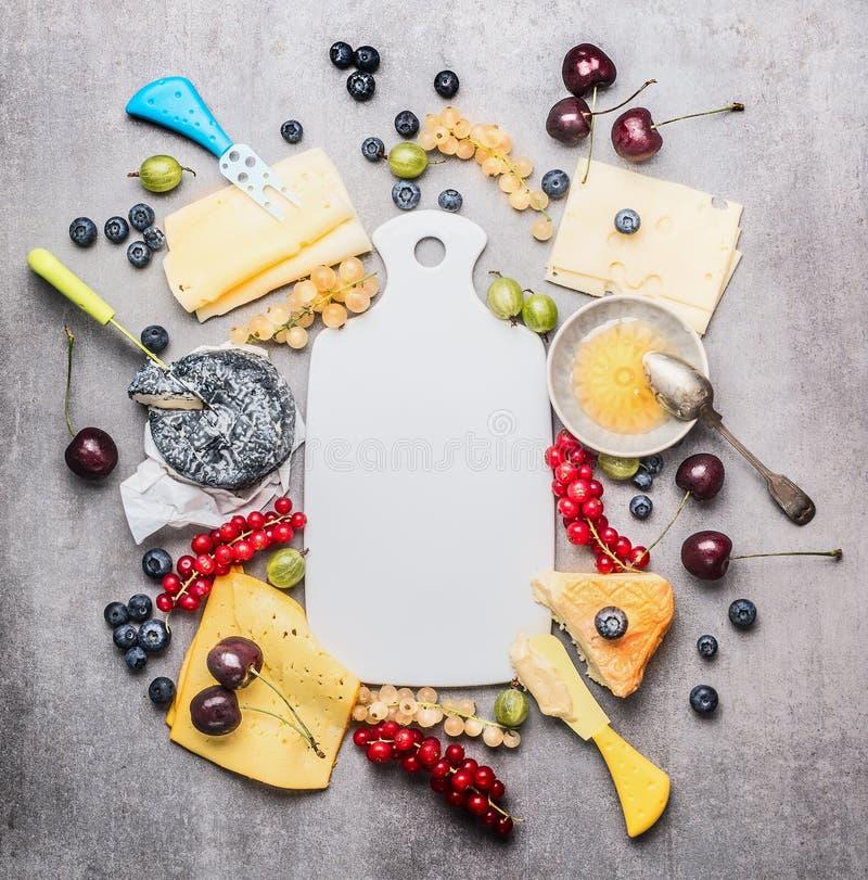 Tabla de cortar blanca en blanco y diverso queso con el cuchillo, las bayas y la miel imágenes de archivo libres de regalías