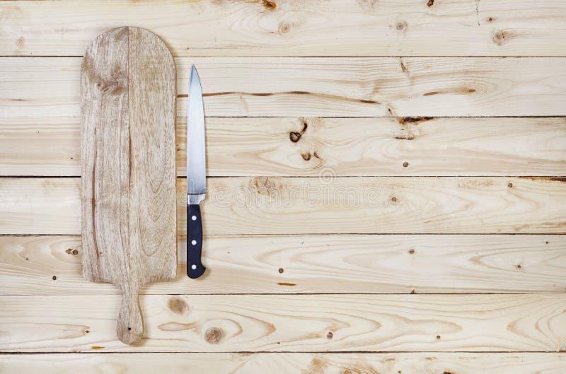 Tabla de cortar con el cuchillo en la tabla de madera Visión superior fotografía de archivo