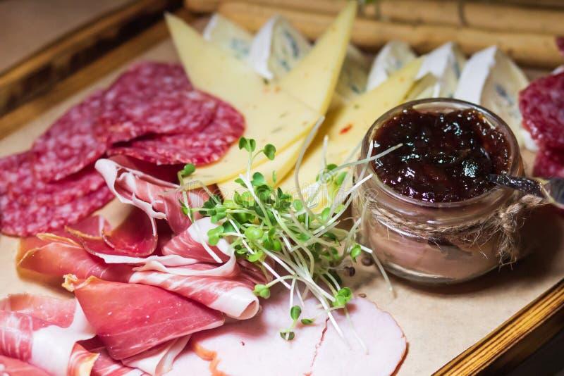 Tabla de cortar con el prosciutto, el salami, el queso, las barras de pan y las aceitunas en el abastecimiento foto de archivo