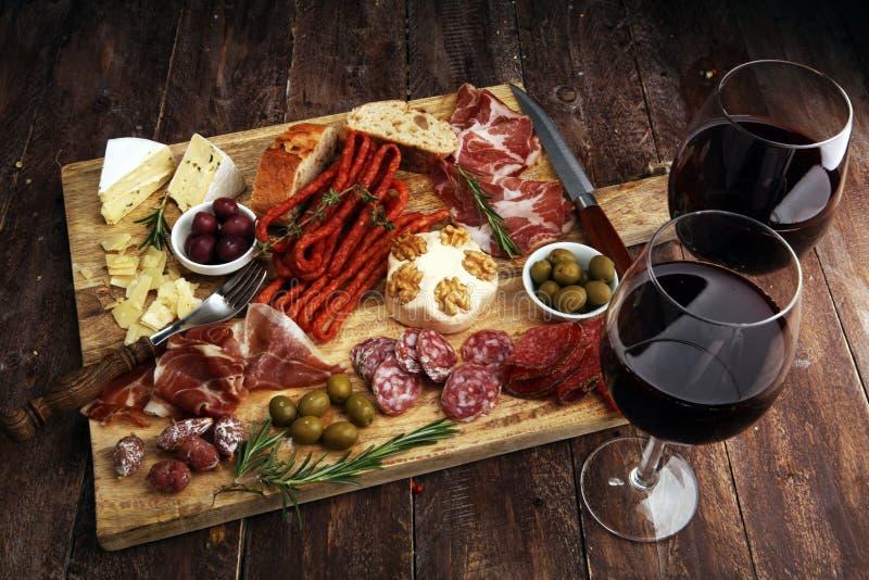 Tabla de cortar con el prosciutto, el salami, el queso, el pan y las aceitunas en fondo de madera oscuro imagenes de archivo