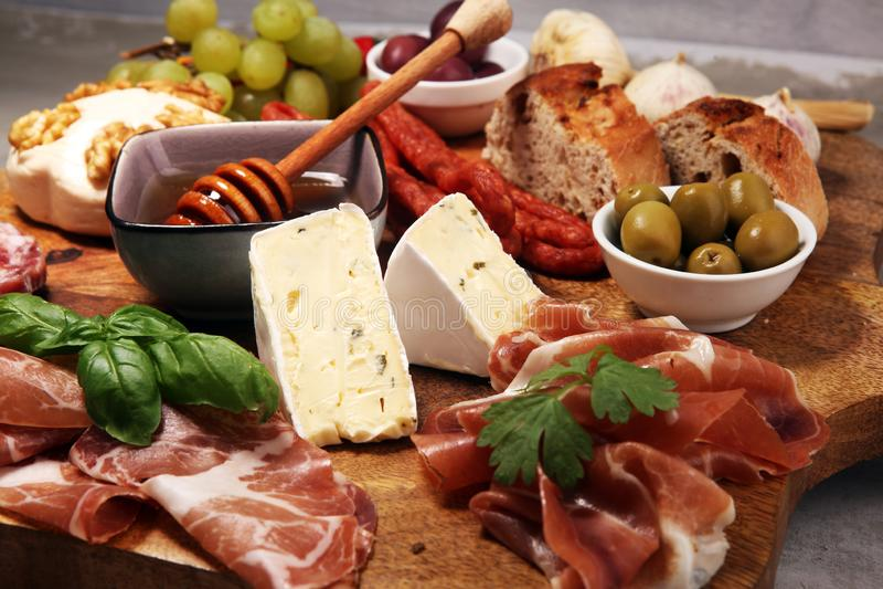 Tabla de cortar con el prosciutto, el salami, el queso, el pan y las aceitunas en fondo de piedra oscuro fotos de archivo