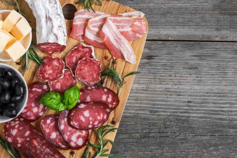 Tabla de cortar con el salami francés, la salchicha ahumada, el tocino, el queso, aceitunas e hierbas en fondo de madera rústico imagen de archivo