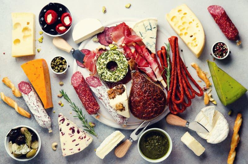 Tabla de cortar con la carne ahumada fría, prosciutto, salami, surtido de quesos, barras de pan, alcaparras, aceitunas en gris foto de archivo libre de regalías