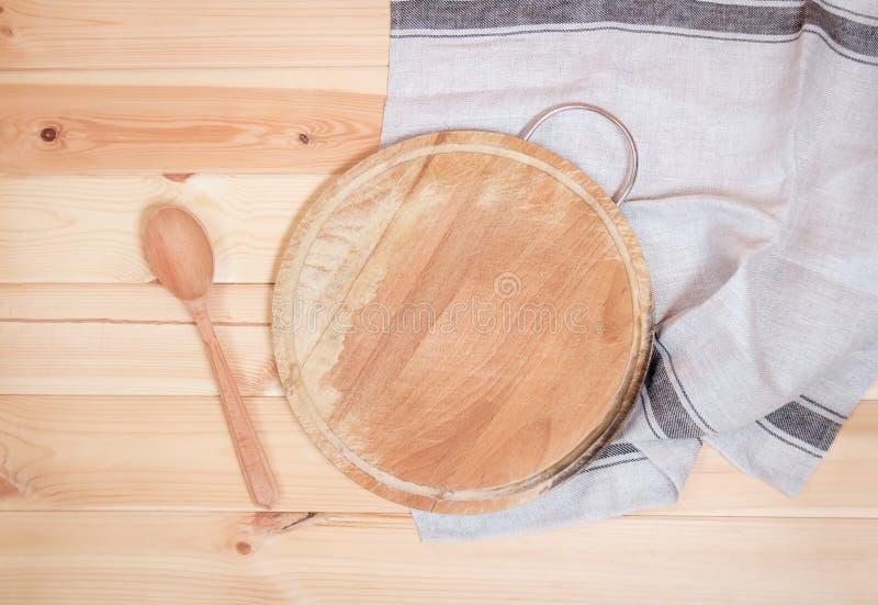 Tabla de cortar con la cuchara de madera y servilleta en fondo de madera fotografía de archivo