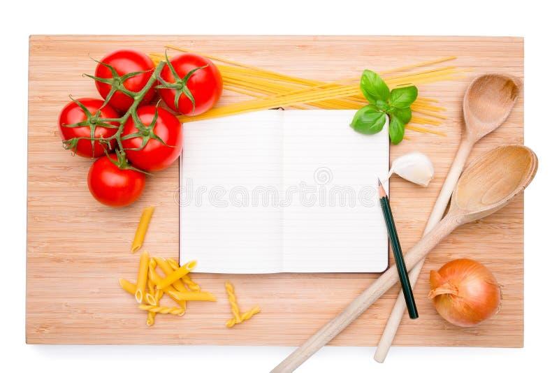 Tabla de cortar de madera con el libro de cocina imágenes de archivo libres de regalías