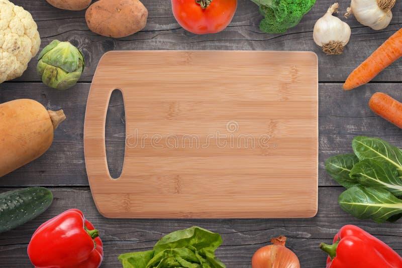 Tabla de cortar de la comida rodeada con las verduras en el escritorio de madera negro fotos de archivo libres de regalías