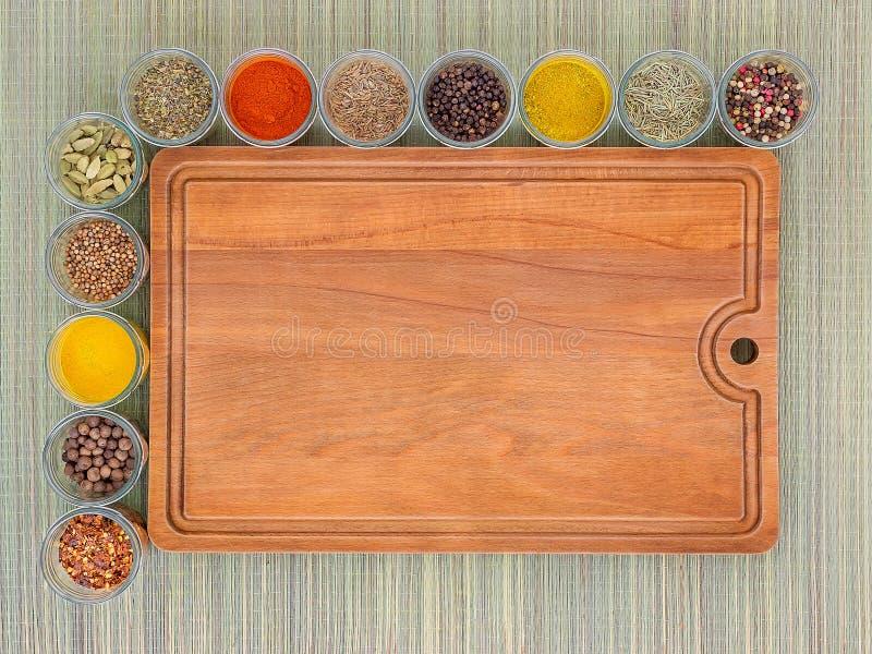 Tabla de cortar de madera de Brown y muchos tarros de cristal con las especias a la izquierda y arriba de ella en un fondo de una fotos de archivo