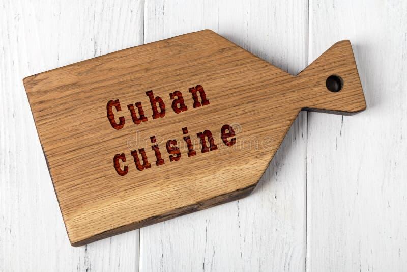 Tabla de cortar de madera con la inscripción Concepto de cocina cubana imagen de archivo