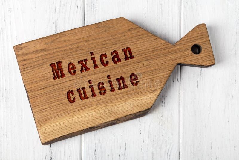 Tabla de cortar de madera con la inscripci?n Concepto de cocina mexicana imagenes de archivo