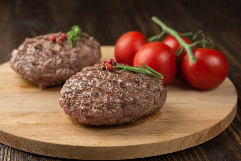 Tabla de cortar de madera recientemente asada a la parrilla del ion de la carne de la hamburguesa imagen de archivo libre de regalías