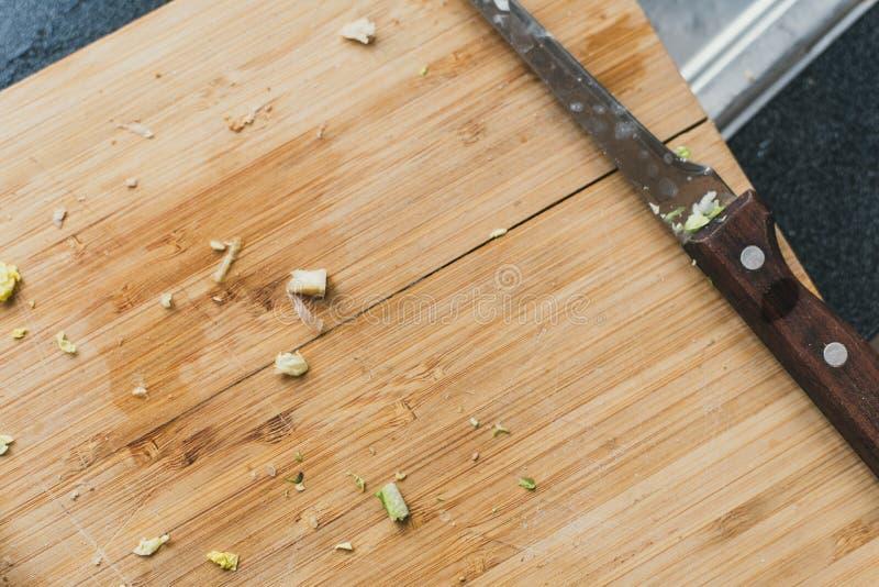 tabla de cortar de madera sucia con un cuchillo Las cebollas cortaron en una tabla de cortar remanente del verdor en un fondo de  imagen de archivo