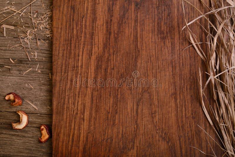 Tabla de cortar rústica de madera vacía con el espacio de la copia de la paja para el texto foto de archivo