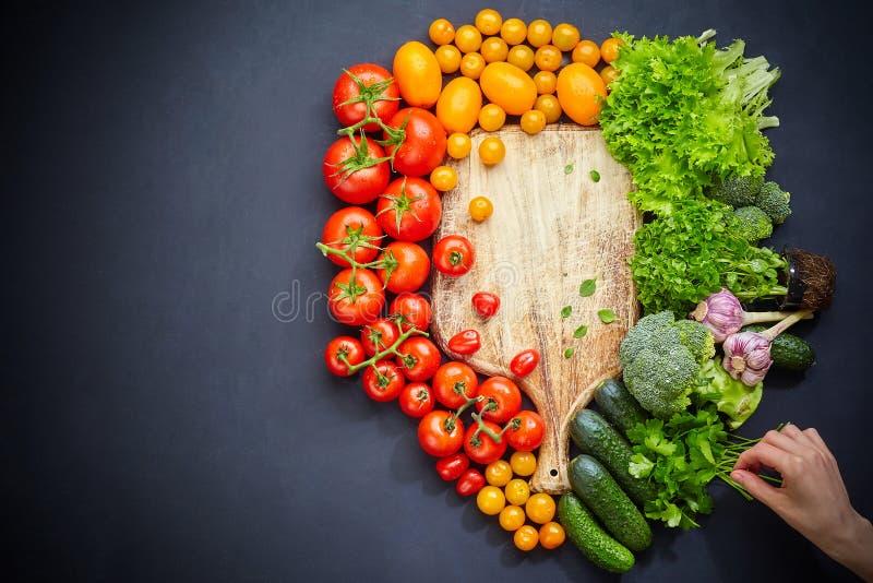 Tabla de cortar rústica vacía rodeada por las diversas verduras crudas para cocinar sano imagenes de archivo