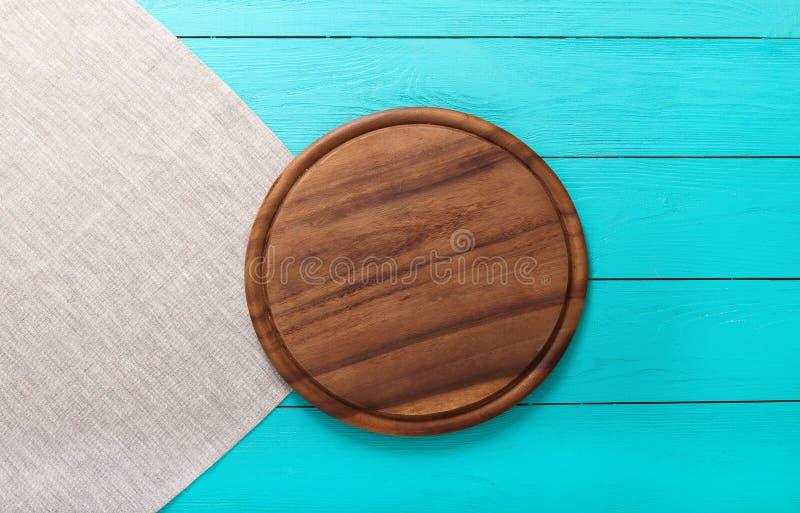 Tabla de cortar redonda de Brown para los platos del día de fiesta en servilleta de lino gris Fondo de madera azul en el restaura imagenes de archivo