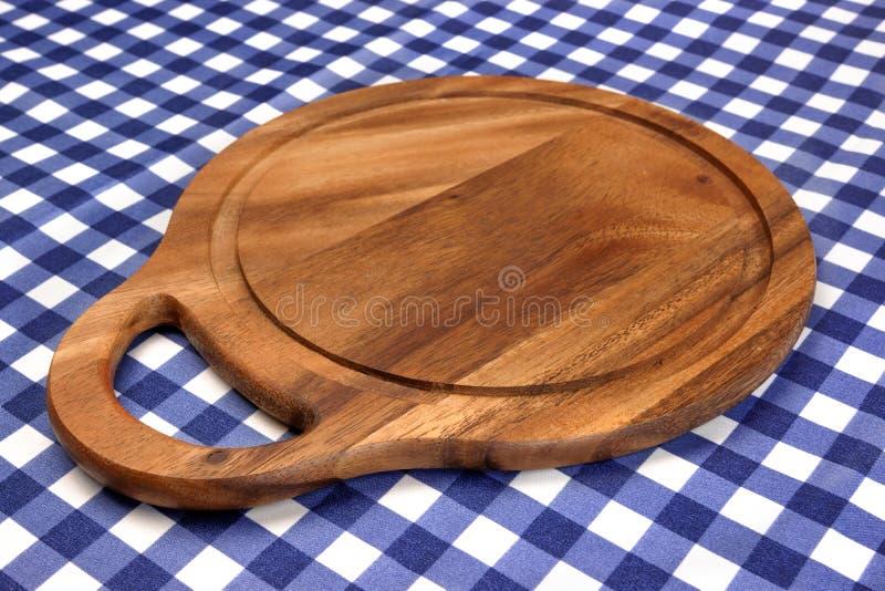 Tabla de cortar redonda de la madera dura vacía en el Tablecl a cuadros azul foto de archivo libre de regalías