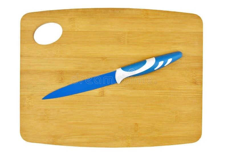 Tabla de cortar y cuchillo de cocina de cerámica imagenes de archivo